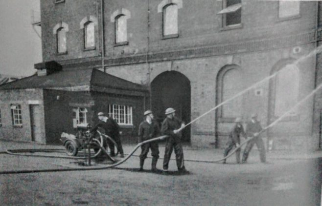 Members of Dowtys Auxiliary fire service practising at the Dowty factory site at Ashchurch WW2